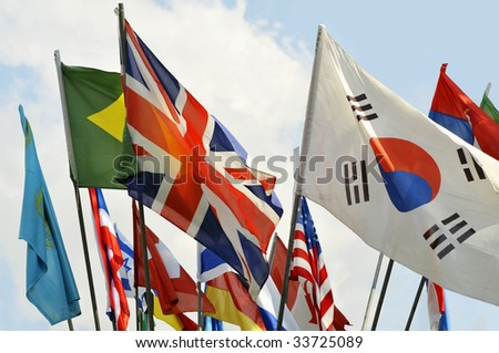 Colorful Flags and a Blue Sky with Clouds on Background
