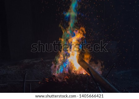 colorful flame on smelting tin and copper to create bronze as a raw material in gong production