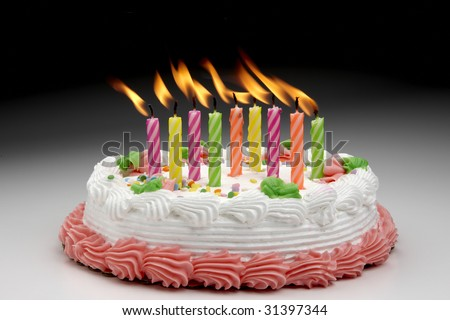 Colorful Flaming candles on a decorated cake