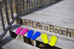 Colorful flip flops on a beach boardwalk
