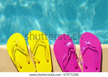 Colorful flip flops on the edge of a swimming pool