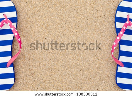 Colorful flipflop pairas a frame on beach sand
