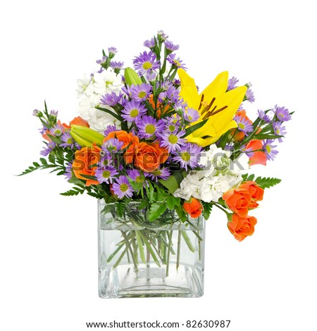 Colorful flower arrangement centerpiece  in square glass vase with roses, daisies and llilies isolated on white