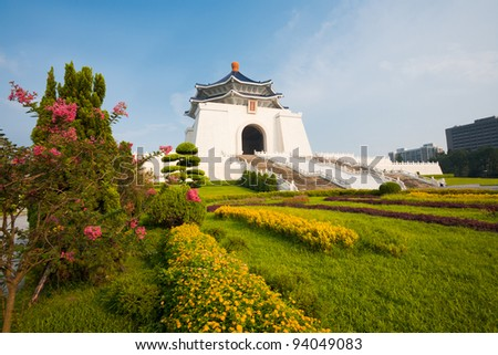 Colorful flowers and grass at the base of the front facade of Chiang Kai Shek Memorial Hall on a clear sunny, blue sky day in Taipei, Taiwan.  Horizontal copy space