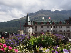 Colorful flowers and historical building in european city center of St. Moritz at alpine landscapes in Switzerland with cloudy blue sky in 2018 warm sunny summer day on August.