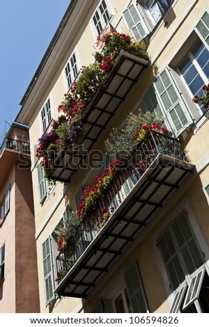 Colorful flowers and plants growing outside balconies of apartment flats in France.