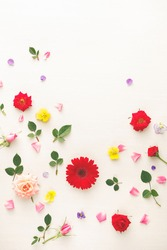 Colorful flowers  background  made of pink and red roses, green leaves, gerbera and pansy flowers on white background. Flat lay, top view