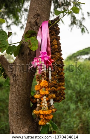 Colorful flowers decoration from previous day that was offered to the spirits in the spirits house hanged on a tree. #1370434814