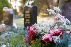 Colorful Flowers in front of a Tombstones in a Cemetery Graveyard