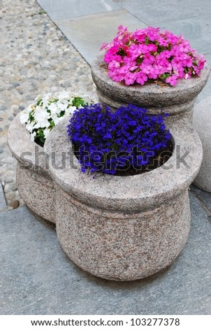 Colorful flowers in granite flower pot as street decoration