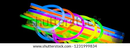 Colorful fluorescent light neon glow stick bracelet strap wristband and tubes on mirror reflection black background. Yellow Blue pink orange green violet glow sticks