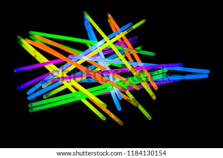 Colorful fluorescent light neon glow stick on mirror reflection black background. Yellow Blue pink orange green violet glow sticks #1184130154