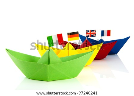 Colorful folded paper boats with European flags isolated over white background