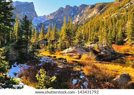 Colorful forest in Rocky Mountain National Park in fall with snow and mountains in background, Colorado, USA