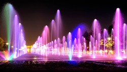 colorful fountain dancing in city park at night against black sky background. Street wide view of splashing water from ground. Moscow city russia landmark