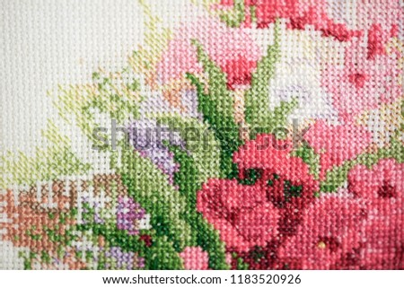 Colorful fragment of cross stitch embroidery with pink flowers. Close up of colorful cross stitch embroidery.               - Shutterstock ID 1183520926