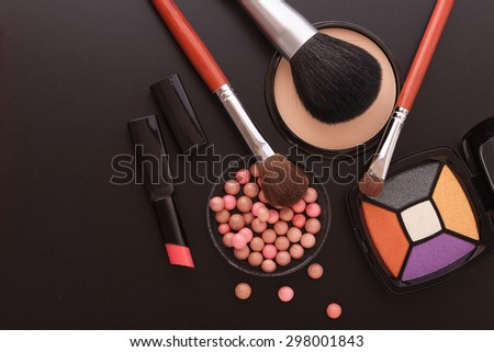 Colorful frame with various makeup products on black texture background. An unusual view, top view, mock up for design. Selective focus.