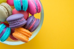 Colorful france macarons on yellow background