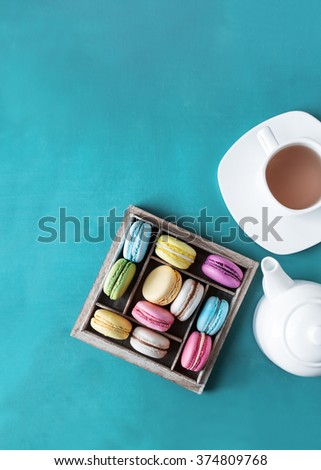 Colorful French macaroons in a wooden gift box. Cup of tea and teapot. Top view. #374809768