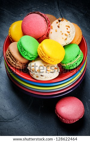 Colorful French macaroons on multicolor plate stack
