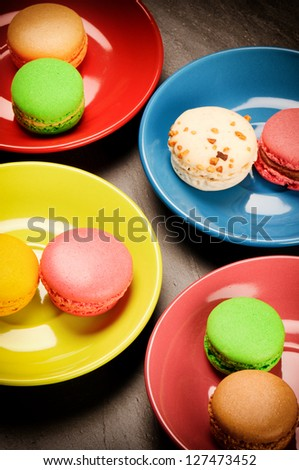 Colorful French macaroons on stone background