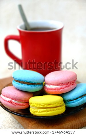 Colorful french Sweet Pastries Macaroons on glass table and red coffee mug on wooden tray.