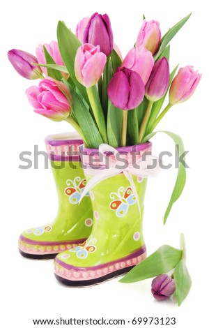 Colorful fresh spring tulips flowers in boots vase on white background - stock photo