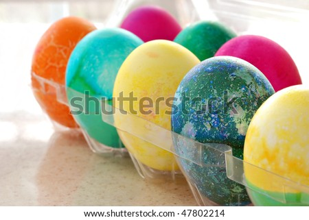 Colorful freshly dyed easter eggs in carton.  Sunny backlighting and extremely shallow dof.  Focus limited to blue egg.
