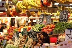 Colorful Fruit and vegetable stand in a Spanish market taken in the famous La Boqueria market in Barcelona, including bananas, pineapples, tomatoes and green beans.