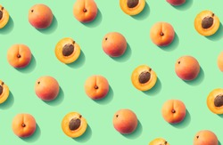 Colorful fruit pattern of fresh apricots on green pastel background, top view, flat lay