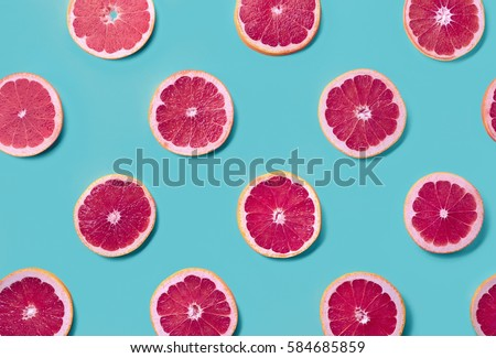 Colorful fruit pattern of fresh grapefruit slices on blue background. From top view