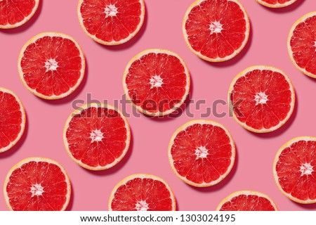 Colorful fruit pattern of fresh grapefruit slices on pink background. Minimal flat lay concept. ストックフォト ©