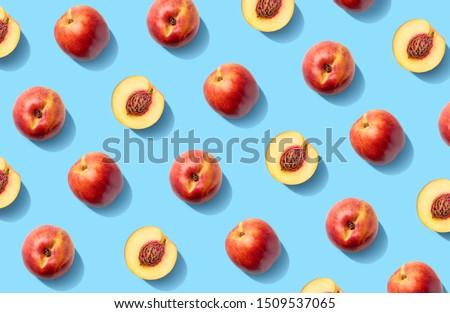 Colorful fruit pattern of fresh nectarines on  blue pastel background