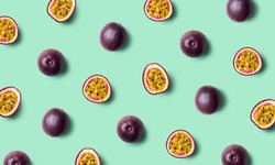 Colorful fruit pattern of fresh passion fruits on green pastel background, top view