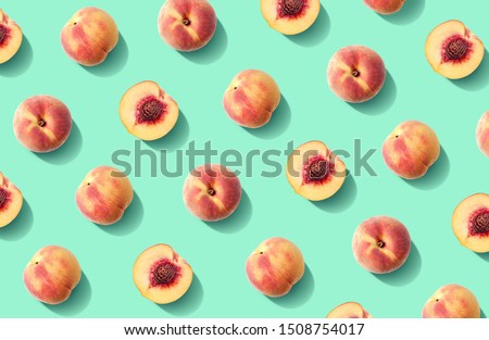 Colorful fruit pattern of fresh peaches on green pastel background