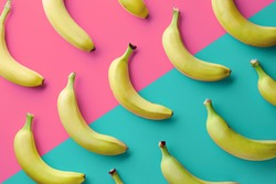Colorful fruit pattern of fresh yellow bananas on pink and blue background. From top view