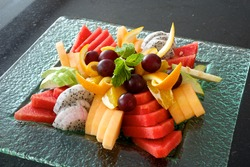 Colorful fruit platter with watermelon, cantaloupe, grapes, oranges, Dragon fruit and mint