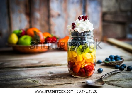 Colorful fruit salad in a jar on rustic wooden background #333913928