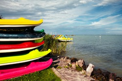 Colorful funny crocodile shaped children canoes and kayaks on the coast of the Lake Balaton on a cloudy summer afternoon. Balaton is a famous tourist destination and the largest lake in Central Europe