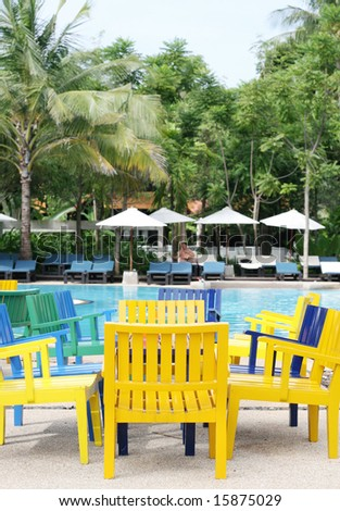 Colorful furniture next to a swimming pool.