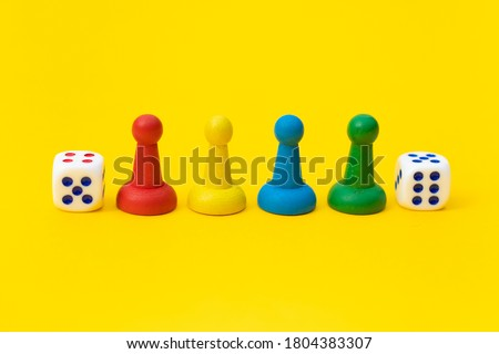 Colorful game chips and two dice are laid out on a yellow background: entertainment, games at home for the whole family, the concept of Board games. Board game. Table games