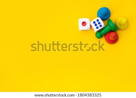 Colorful game chips and two dice are laid out on a yellow background: entertainment, games at home for the whole family, the concept of Board games. Board game. Table games, space for text