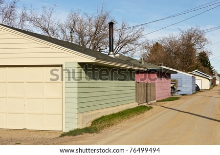 Colorful garages that border a dirt alley glow in late day sun in a city in Montana