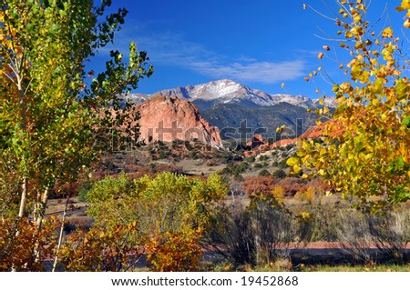 Colorful Garden of the Gods Park near Colorado Springs, Colorado with golden leaved trees and snow covered Pikes Peak