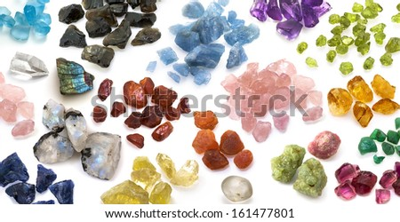Colorful gemstones background. Large variety of natural raw, uncut precious and semiprecious gems on the white background.