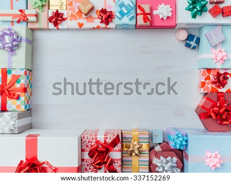Colorful gift boxes framing a blank copy space on a desktop, top view, Christmas and celebrations concept #337152269