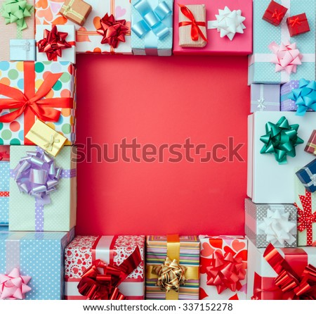 Colorful gift boxes framing a red blank copy space on a desktop, top view, Christmas and celebrations concept #337152278