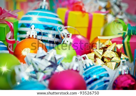 Colorful gift boxes intermingled with shining Christmas balls and bows. - stock photo