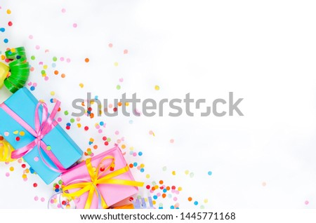 Colorful Gift boxes, paper confetti and twirled party serpentine on a white background with copyspace, greeting card and party invitation template design for New Year Christmas wedding or birthday