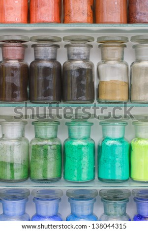 Colorful glass bottles of paint pigments on glass shelves